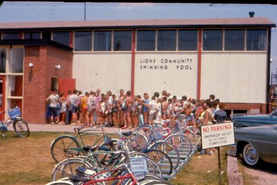 Swimmers lined up outside the public pool building