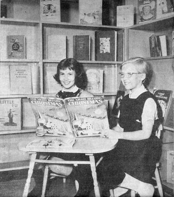 Two Girls pose with a book in the new Children's Library