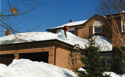 Brendan Saunders shovels snow off his roof following a grand snowstorm in 1999