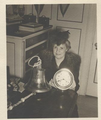 Oakville resident Mrs. Marlatt displays ship's bell and chronometer