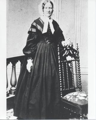Senior woman standing behind dark wood chair.