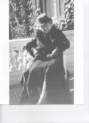 Older woman sitting in a chair on a patio outside. She is wearing black or dark coloured garments and a hat.